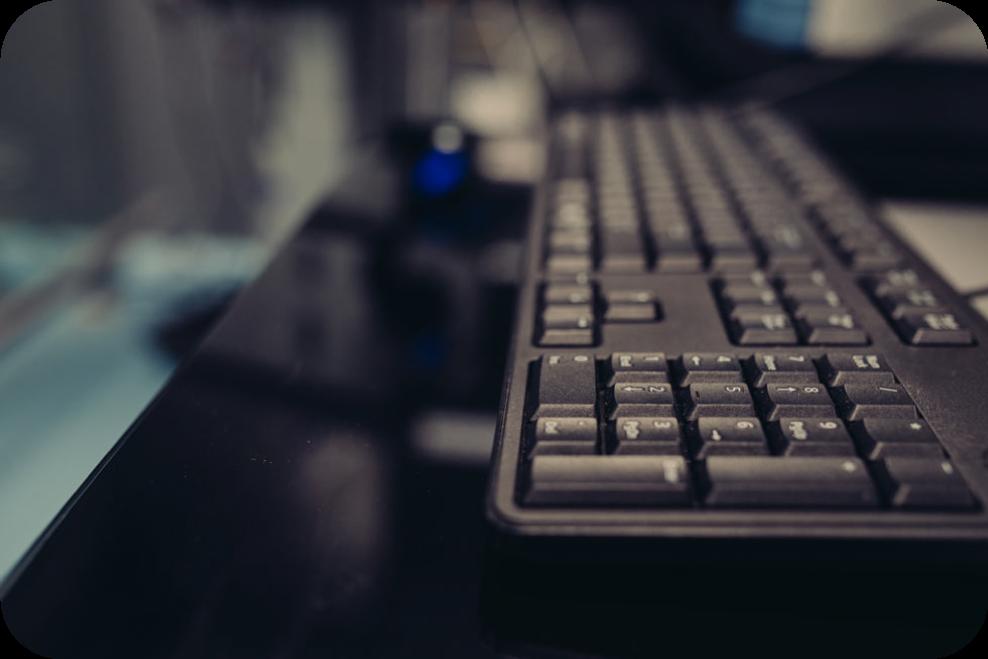 black plastic computer keyboard on a black desk