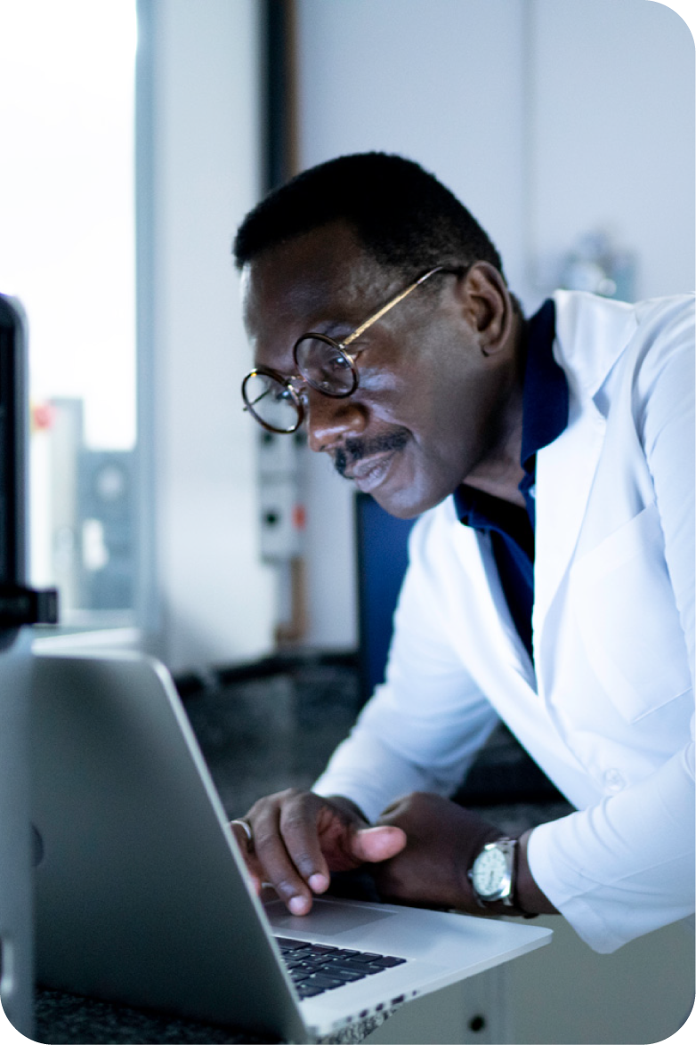 scientist in a white coat looking at a laptop