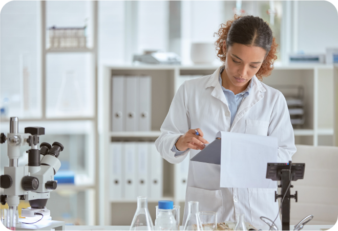 scientist stood in a lab wearing a white coat examining data on a clip board