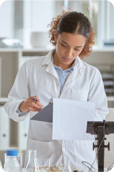 scientist in a white coat examing informtion on a clip board