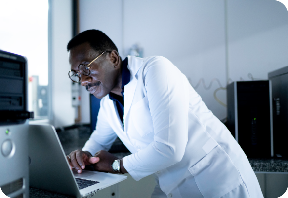 male scientist wearing a white coat looking at a laptop screen